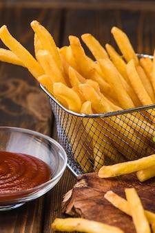 Batatas fritas com molho em uma bandeja de madeira
