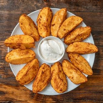 Batatas fritas com molho mexicano no prato.