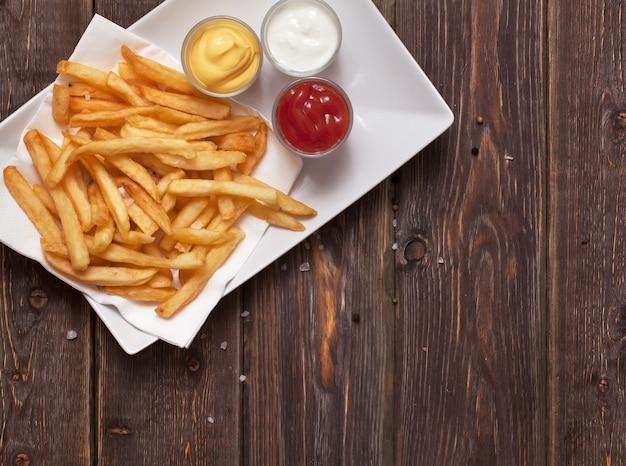 Batatas fritas com molho na mesa de madeira.