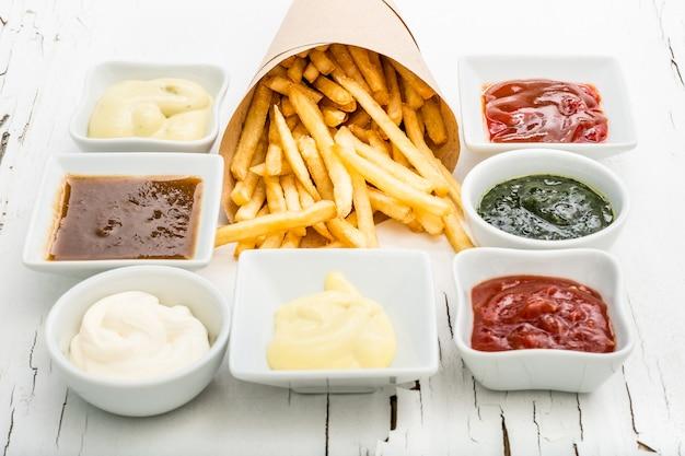 Batatas fritas com molhos no fundo branco, vista superior