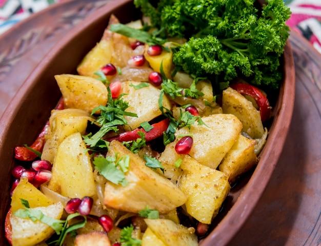 Batatas fritas com pedaços de carne em uma panela de barro. cozinha européia.
