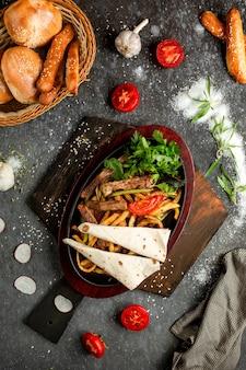 Batatas fritas com pedaços de carne frita em uma panela de barro