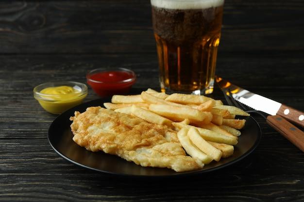 Batatas fritas com peixe e cerveja em fundo de madeira