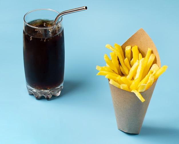 Batatas fritas com refrigerante no fundo azul