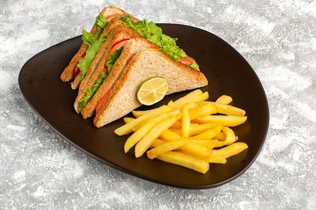 Batatas fritas com sanduíches dentro de um prato marrom