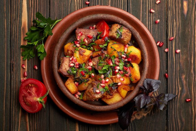 Batatas fritas com sementes de carne e romã, em um prato de barro, sobre um fundo de madeira com ervas e tomate