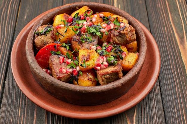 Batatas fritas com sementes de carne e romã, em um prato de barro, sobre um fundo de madeira