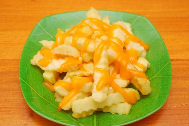 Batatas fritas com temperos de queijo são servidas em uma mesa de madeira