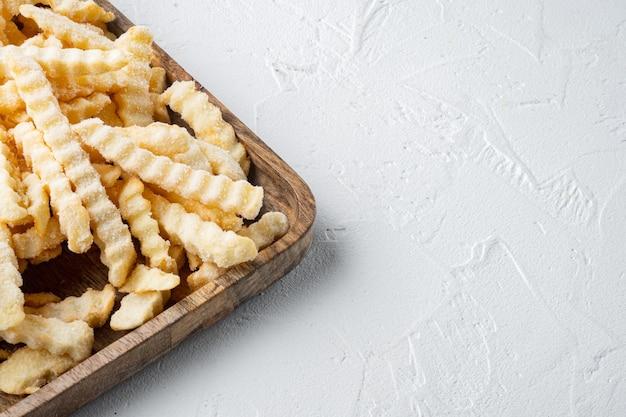 Batatas fritas congeladas em uma bandeja de madeira