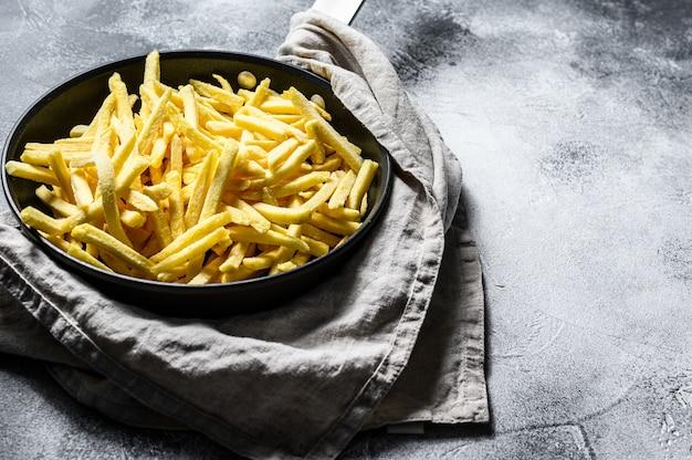 Batatas fritas congeladas em uma frigideira.