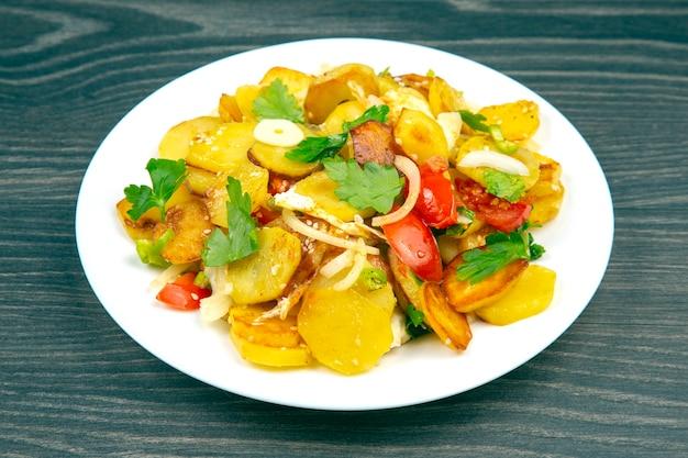 Batatas fritas cozidas com ervas e vegetais em um prato branco sobre uma mesa de madeira