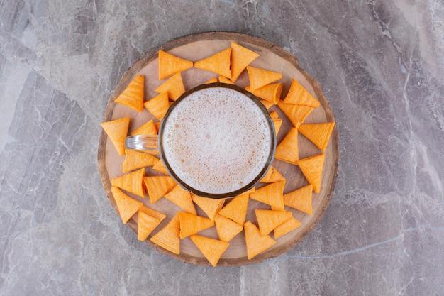 Batatas fritas crocantes com cerveja gelada na peça de madeira. foto de alta qualidade