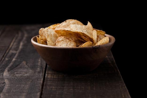 Batatas fritas crocantes de pimenta deliciosa em uma tigela de madeira com fundo de madeira