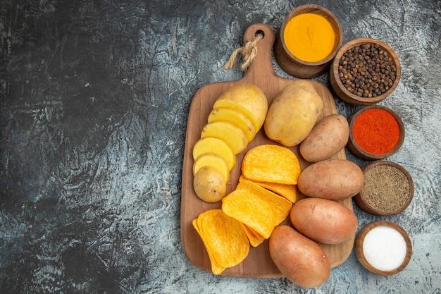 Batatas fritas crocantes e batatas não cozidas em uma tábua de madeira e temperos diferentes no lado esquerdo da mesa cinza