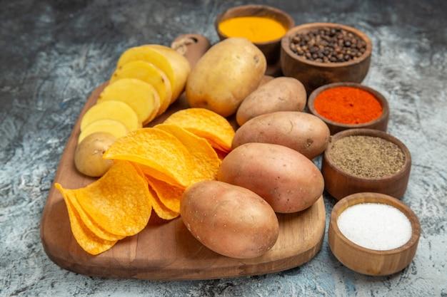 Batatas fritas crocantes e batatas não cozidas na tábua de madeira e temperos diferentes na mesa cinza