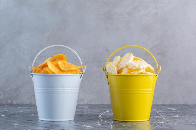Batatas fritas crocantes e chips de queijo em baldes, na superfície do mármore