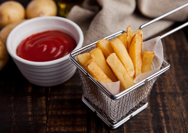 Batatas fritas de batatas fritas na fritadeira com ketchup