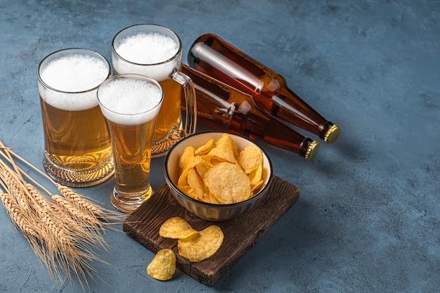 Batatas fritas de cerveja e espigas de trigo em um fundo azul escuro espaço de vista lateral para cópia