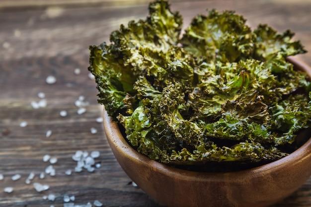 Batatas fritas de couve verde caseiras assadas com vinagre balsâmico em uma tigela sobre fundo de madeira rústico. lanche saudável. foco seletivo.