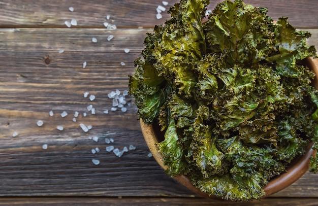 Batatas fritas de couve verde caseiras assadas com vinagre balsâmico em uma tigela sobre fundo de madeira rústico. lanche saudável. vista do topo.