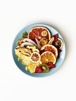 Batatas fritas de frutas secas em placa de cerâmica redonda em branco isolado. vista superior, configuração plana.