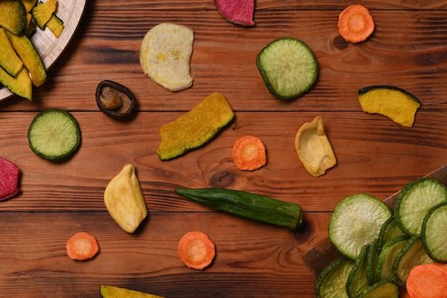 Batatas fritas de legumes secos com cogumelos quiabo, cenoura, abóbora, beterraba e shiitake em fundo de madeira.