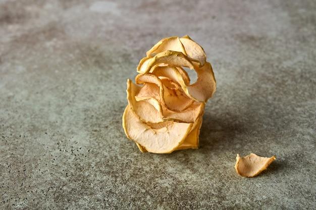 Batatas fritas de maçã desidratadas em um fundo de madeira texturizado fechar o espaço da cópia