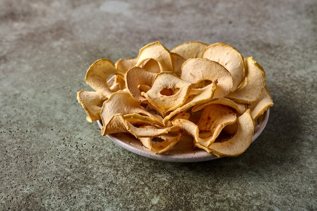 Batatas fritas de maçã desidratadas no prato com fundo de madeira texturizado close-up