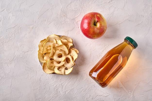Batatas fritas de maçã desidratadas no prato de maçã e garrafa com suco na parte superior do fundo de madeira clara