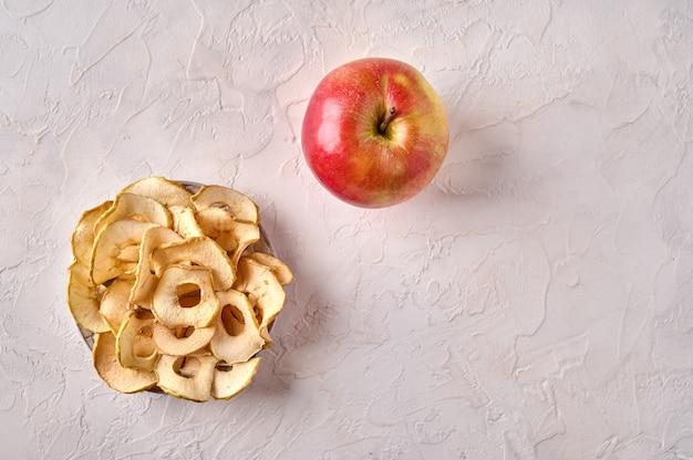 Batatas fritas de maçã desidratadas no prato e maçã na luz de fundo de madeira, vista superior, espaço de cópia