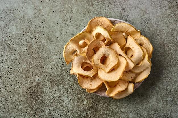 Batatas fritas de maçã desidratadas no prato no espaço de cópia da vista superior do plano de fundo de madeira texturizado
