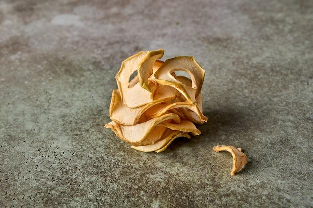 Batatas fritas de maçã desidratadas no prato no fundo de madeira texturizado fechem o espaço da cópia