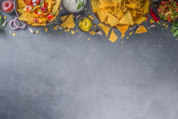 Batatas fritas de nachos com molhos diversos, tradicional petisco mexicano no prato