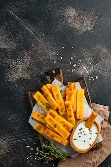 Batatas fritas de polenta caseiras com sal marinho, parmesão, tomilho, alecrim com molho de iogurte. polenta frita italiana típica. palitos de milho frito. antigo fundo escuro de concreto. vista do topo
