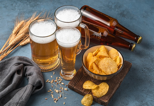 Batatas fritas de três canecas cheias de cerveja e garrafas de cerveja em um fundo azul escuro