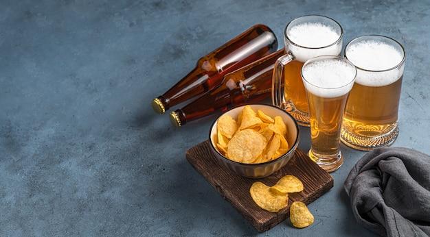 Batatas fritas de três canecas de cerveja e garrafas de cerveja em um fundo azul escuro Foto Premium