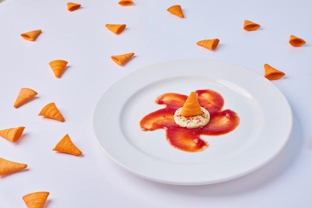 Batatas fritas de triângulo servidas com molho de tomate vermelho e biscoitos no branco.
