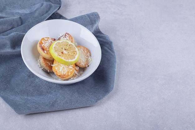 Batatas fritas decoradas com queijo ralado e limão na chapa branca.