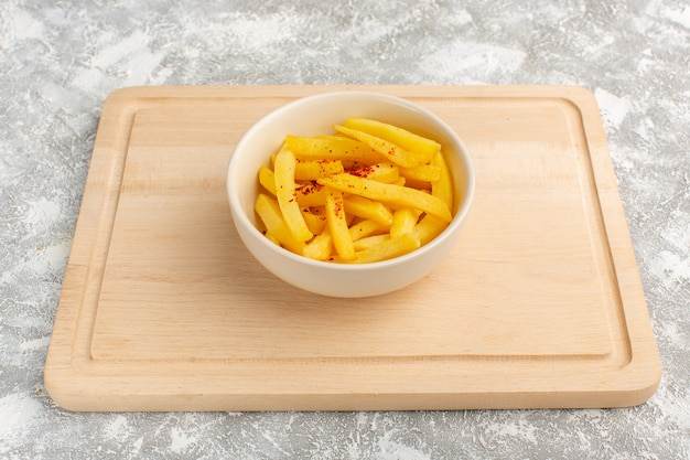 Batatas fritas dentro de prato branco em cinza