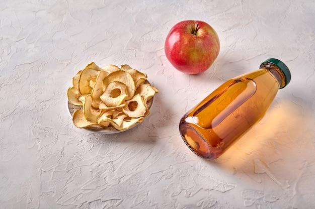 Batatas fritas desidratadas de maçã no prato e garrafa com suco na luz de fundo de madeira fechar