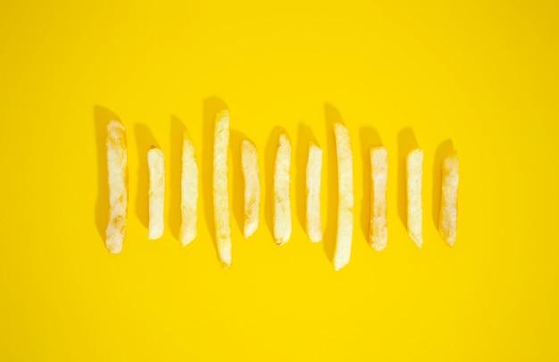 Batatas fritas douradas em fundo amarelo
