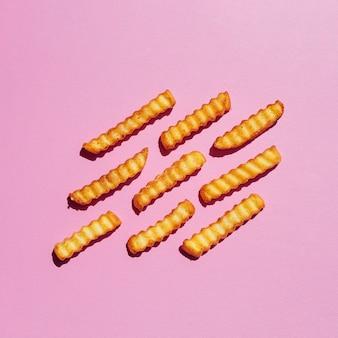 Batatas fritas douradas no fundo rosa