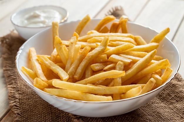 Batatas fritas douradas quentes com molho em um fundo de madeira. comida caseira rústica.