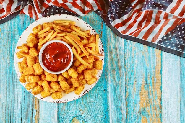 Batatas fritas e batata tater na mesa de madeira para o feriado americano.