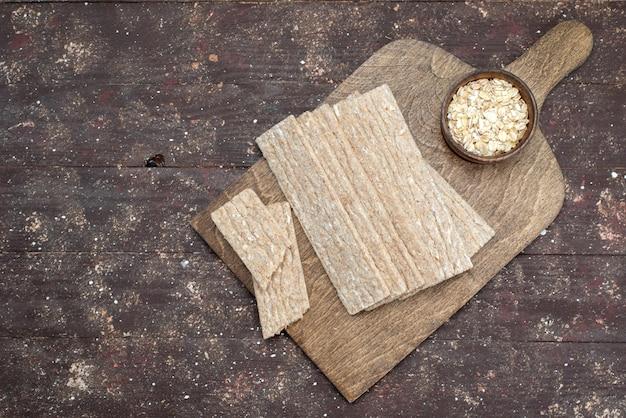 Batatas fritas e bolachas de vista superior formadas há muito tempo na mesa de madeira