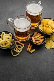 Batatas fritas e canecas de cerveja de alto ângulo