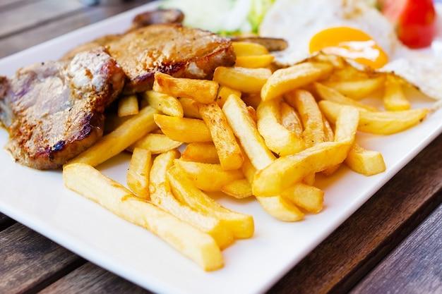 Batatas fritas e carnes fritas, ovo frito.