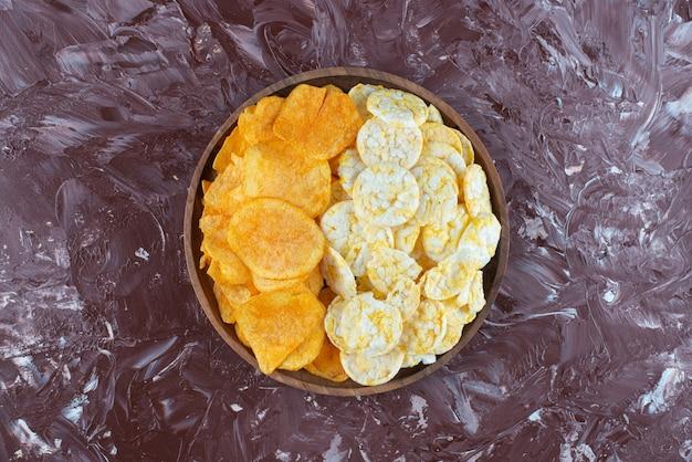 Batatas fritas e chips de queijo no prato em mármore.