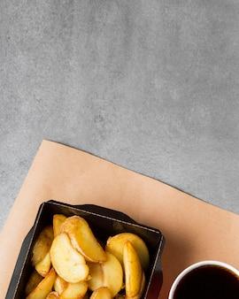 Batatas fritas e coca de alto ângulo com cópia-espaço