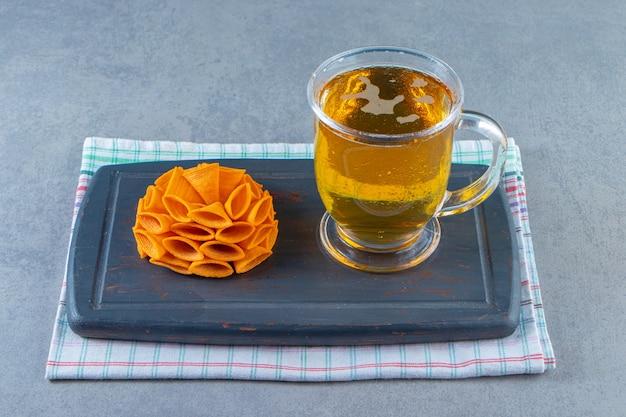 Batatas fritas e copo de cerveja em uma bandeja sobre a toalha, sobre a superfície de mármore.